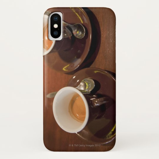 two cups of freshly brewed espresso coffee on a blackberry case
