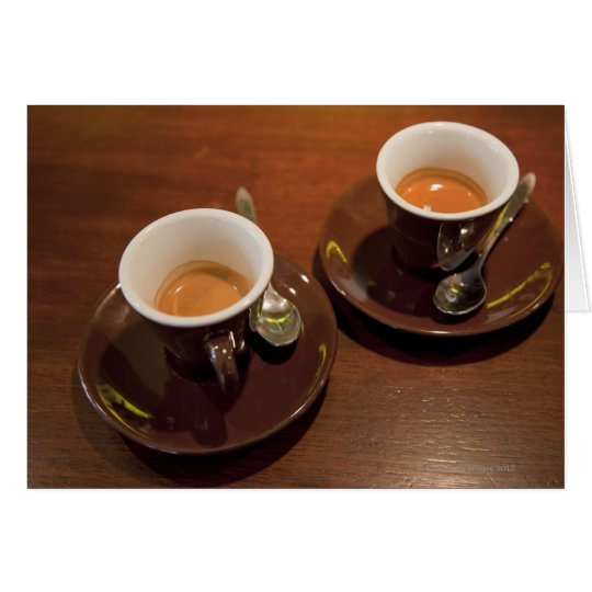 two cups of freshly brewed espresso coffee on a card