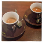 two cups of freshly brewed espresso coffee on a ceramic tile