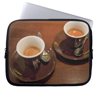 two cups of freshly brewed espresso coffee on a laptop sleeves