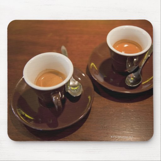two cups of freshly brewed espresso coffee on a mouse pad
