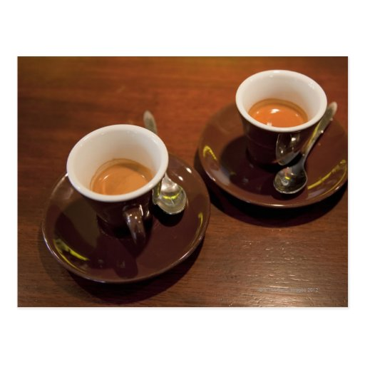 two cups of freshly brewed espresso coffee on a postcards