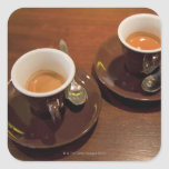 two cups of freshly brewed espresso coffee on a square stickers