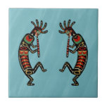 "Two Dancing Flute-Playing Kokopelli Figures Tile<br><div class=""desc"">(Design, Image, and Concept &#169; 2012 Deborah Dalio.) — Kokopelli Pacific Northwest Tour 2012 Collection — Kokopelli, Hopi god of fertility, is on a world tour. His first stop is the Pacific Northwest, land of totem poles. This ceramic tile shows two Kokopelli figures, painted in the style of Pacific Northwest...</div>"