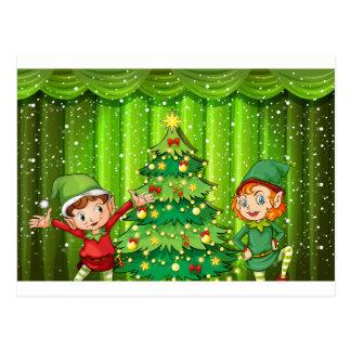 Two elves near the christmas tree postcard
