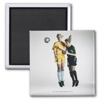 Two female soccer players in mid air heading 2 inch square magnet