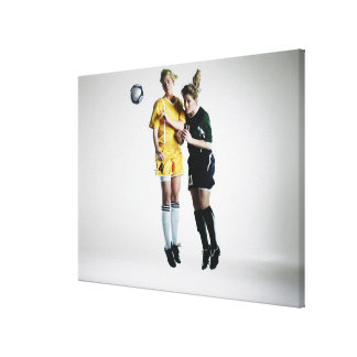 Two female soccer players in mid air heading canvas print