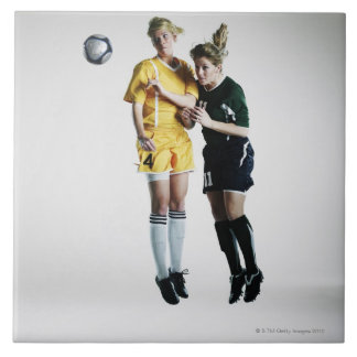 Two female soccer players in mid air heading ceramic tile