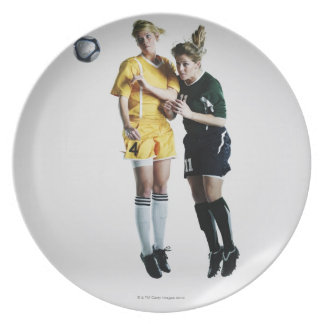 Two female soccer players in mid air heading plates