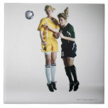 Two female soccer players in mid air heading large square tile