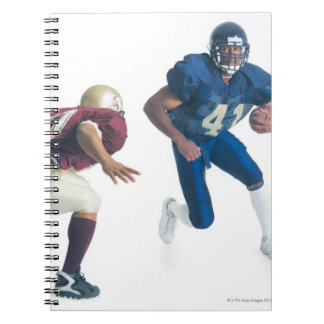 two football players from opposing teams are notebook