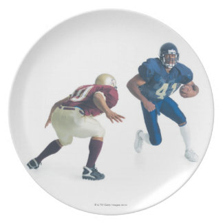 two football players from opposing teams are dinner plate