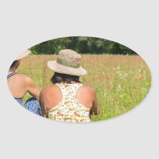 Two friends sitting together in meadow.JPG Oval Sticker