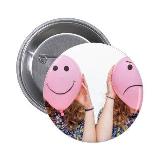 Two girls hold pink balloon with facial expression pinback button