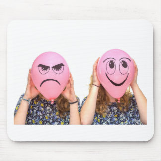 Two girls holding pink balloons with expressions mouse pad