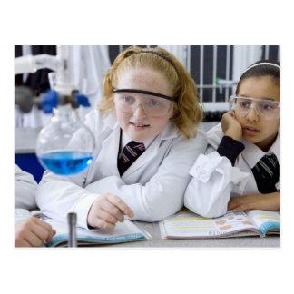 Two girls in school uniform wearing lab coats postcard