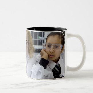 Two girls in school uniform wearing lab coats Two-Tone coffee mug