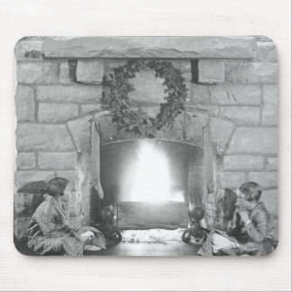Two girls sitting by a fireplace at Christmas Mouse Pad