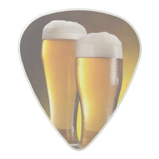 Two glasses of beers on a wooden table acetal guitar pick