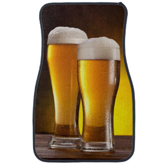 Two glasses of beers on a wooden table car floor mat