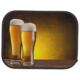 Two glasses of beers on a wooden table car mat