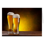 Two glasses of beers on a wooden table greeting card