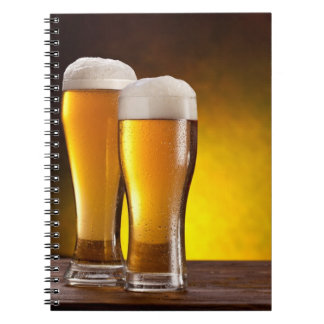 Two glasses of beers on a wooden table notebook