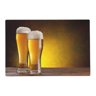 Two glasses of beers on a wooden table laminated placemat