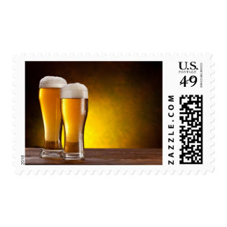 Two glasses of beers on a wooden table postage stamp