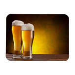 Two glasses of beers on a wooden table rectangular photo magnet