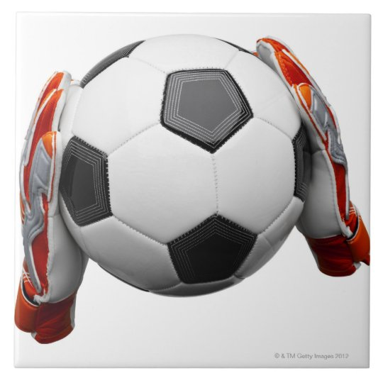 Two goal keepers gloves holding a football ceramic tile