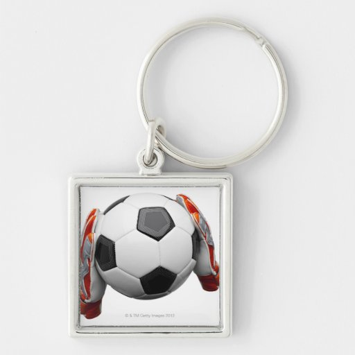Two goal keepers gloves holding a football key chain