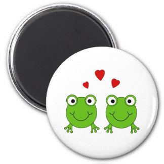 Two green frogs with red hearts. 2 inch round magnet