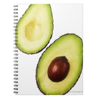 Two halves of an an avocado, on white notebook