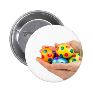 Two hands holding  painted easter eggs on white button