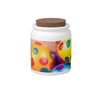 Two hands holding  painted easter eggs on white candy jar