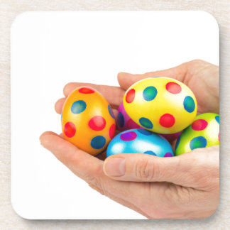 Two hands holding  painted easter eggs on white drink coaster