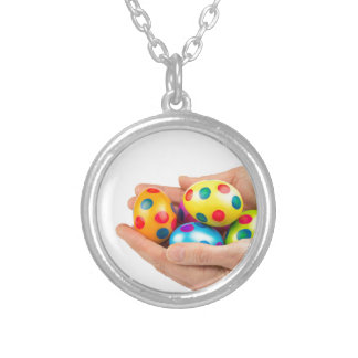 Two hands holding  painted easter eggs on white silver plated necklace