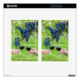 Two hands toasting with red wine near blue grapes kindle fire skins
