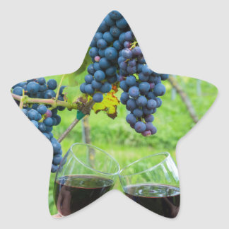 Two hands toasting with red wine near blue grapes star sticker