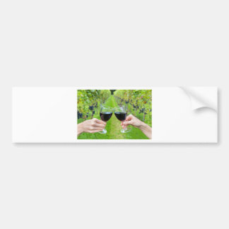 Two hands toasting with wine glasses in vineyard bumper sticker