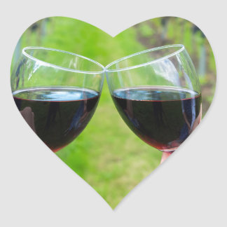 Two hands toasting with wine glasses in vineyard heart sticker