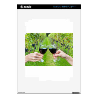 Two hands toasting with wine glasses in vineyard iPad 3 decal