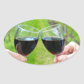 Two hands toasting with wine glasses in vineyard oval sticker