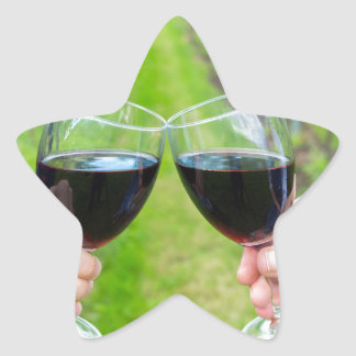 Two hands toasting with wine glasses in vineyard star sticker