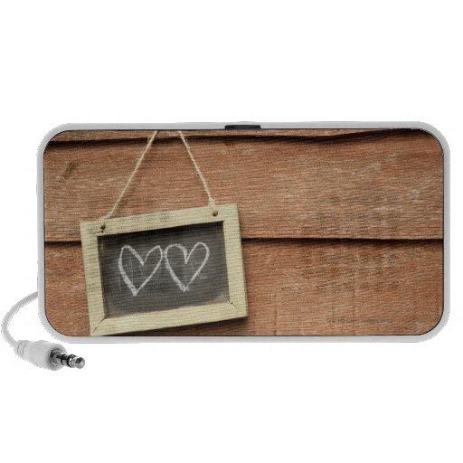 Two hearts drawn on small blackboard on garden mp3 speaker