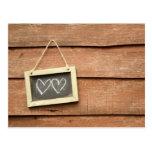 Two hearts drawn on small blackboard on garden postcard