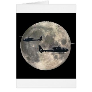 two helicopters silhouetted by a full moon