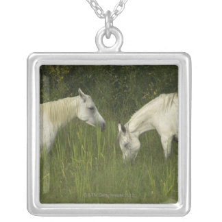 Two horses eating grass pendants
