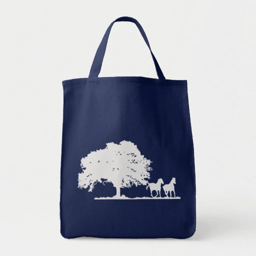 Two horses with large tree in field bags